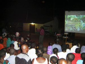 An eager audience follows the pictures and words on the screen.