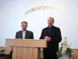 Gabor (left) shares his testimony in Hungarian, while it is translated into Romanian by the man on the right.